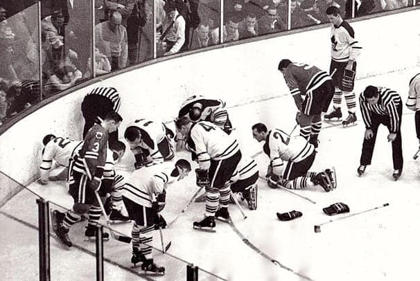 Jääkiekkojoukkueen pelaajat ja tuomarit etsivät pelaajan pudonnutta piilolinssiä jäältä kaukalossa.