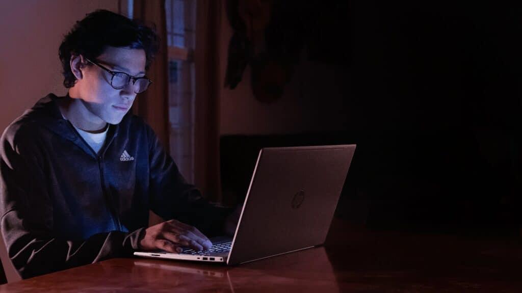 Nuori silmälasipäinen mies tietokoneen äärellä hämärässä.