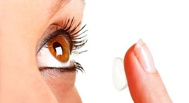Nainen laittamassa piilolinssiä silmään