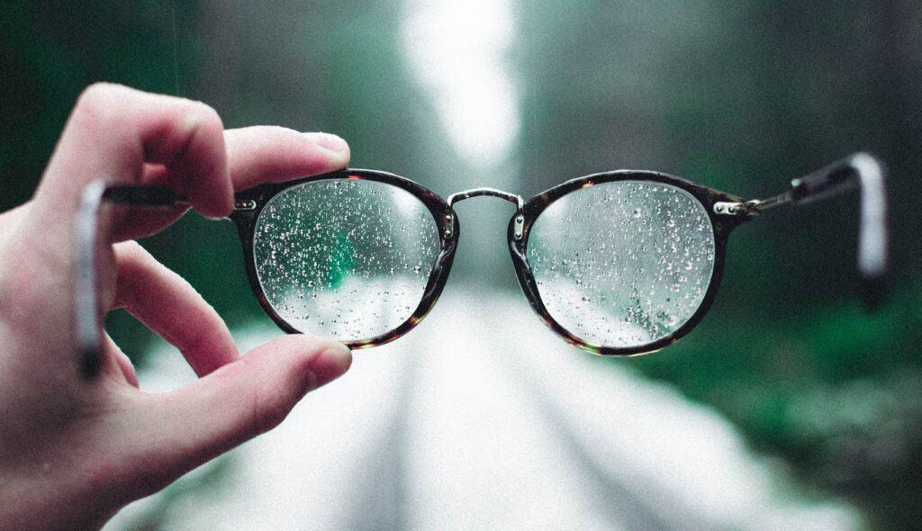 Henkilö pitää kädessään silmälaseja, joissa on vesipisaroita.