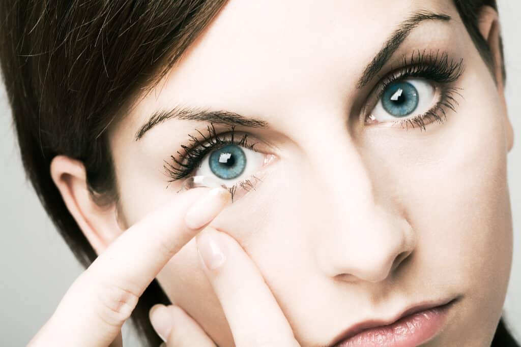 Lähikuva sinisilmäisestä naisesta laittamassa piilolinssiä silmäänsä.