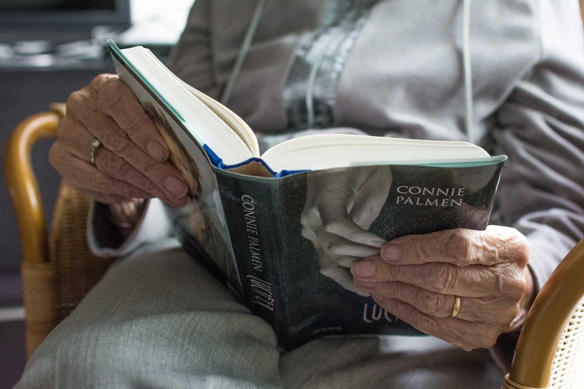 Iäkäs ihminen lukemassa kirjaa